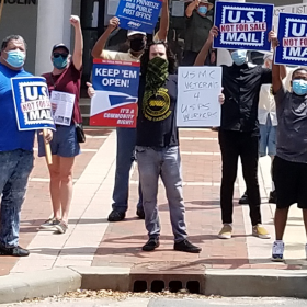 """Crowd stands outside a Post Office holding """"U.S. Mail Not For Sale"""" signs. In the center a man in an APWU tshirt holds two signs. one says """"keep em open"""" the other says USMC veterans 4 USPS workers"""