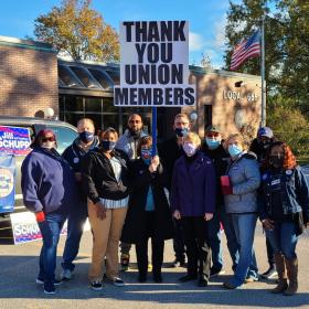 "Group of postal workers with ""Thank you union members"" sign"